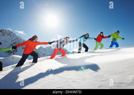 Les amis d'autres tirant chaque montée dans la neige, Kuhtai, Autriche Banque D'Images
