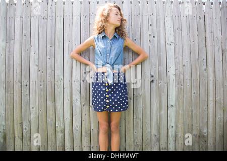 Portrait of teenage girl en face de clôture en bois