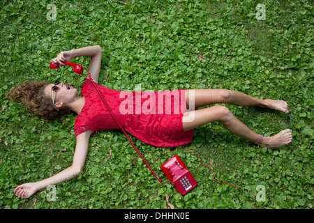 Teenage girl lying on grass avec téléphone rouge Banque D'Images