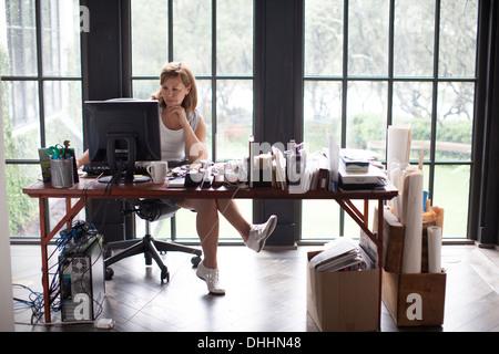 Femme mature à la maison travailler sur ordinateur personnel Banque D'Images