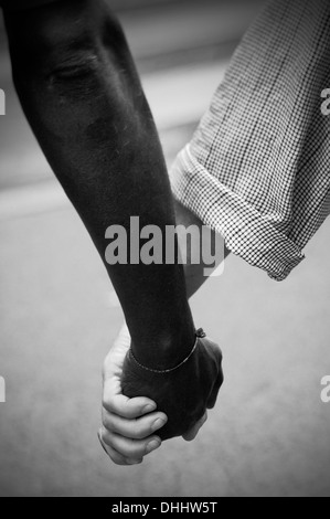 L'Interracial couple walking hand in hand Banque D'Images