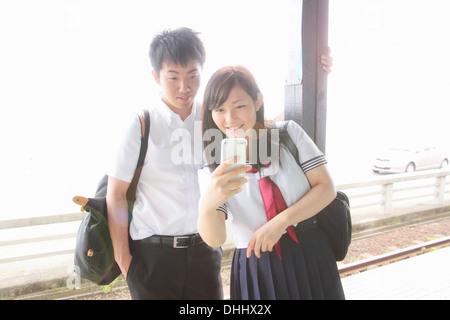 Jeune couple sur un quai de gare looking at smartphone Banque D'Images