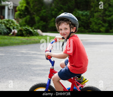 Portrait of young boy riding bicycle on driveway Banque D'Images