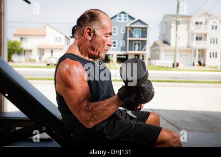 Portrait of muscular man lifting dumb bells Banque D'Images