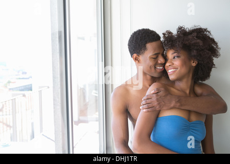 Portrait of young couple par fenêtre, homme avec bras autour de femme Banque D'Images