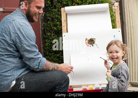Père fricoter mettre la peinture sur le visage de fille Banque D'Images