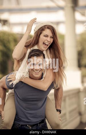 Jeune couple rire dans la ville piggy back ride Banque D'Images
