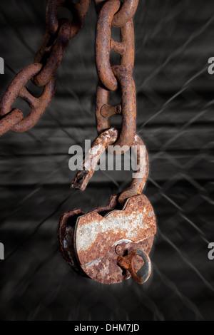 Big old rusty metal cadenas ouvert avec une clé accrochée à un chaîne de caractères gras Banque D'Images