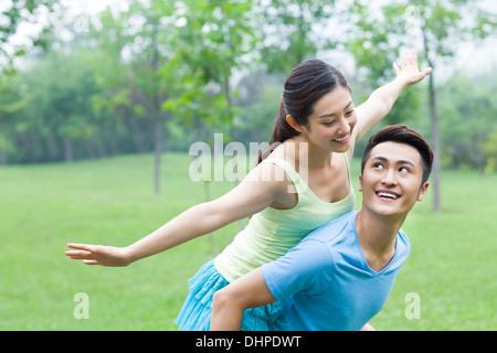 Jeune homme donnant à son amie un piggy back ride Banque D'Images