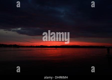 Soirée coucher du soleil rouge couleurs et nuages sur le lac de James en Angola, Indiana USA. Banque D'Images