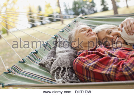 Loving mature couple lying in hammock at park Banque D'Images