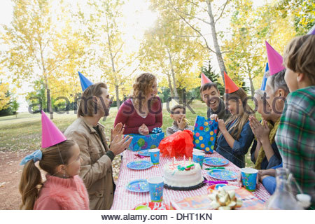 Professionnels multi-generation family celebrating girls birthday in park Banque D'Images