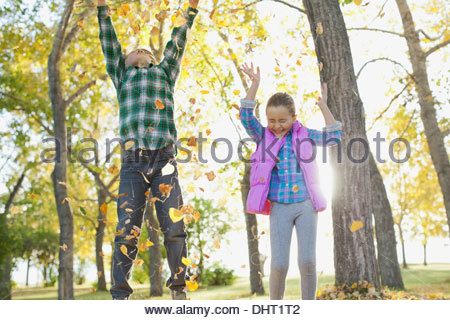Cheerful siblings Playing with leaves in park au cours de l'automne Banque D'Images