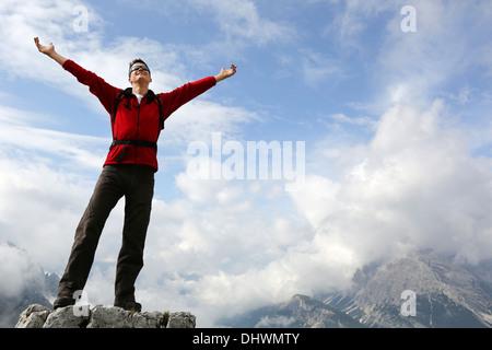 Jeune alpiniste debout sur un rocher et jouissant de la liberté dans les montagnes Banque D'Images