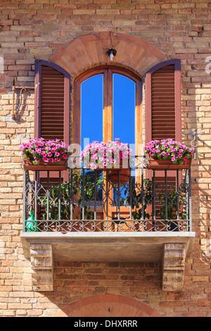 Balcon italien avec des fleurs à San Gimignano. Une colline de la ville médiévale dans la province de Sienne, Toscane
