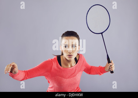 Portrait of young woman contre fond gris. Athlète fit jouer au badminton. Banque D'Images