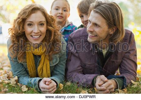 Portrait de femme heureuse avec la famille lying on grass in park Banque D'Images