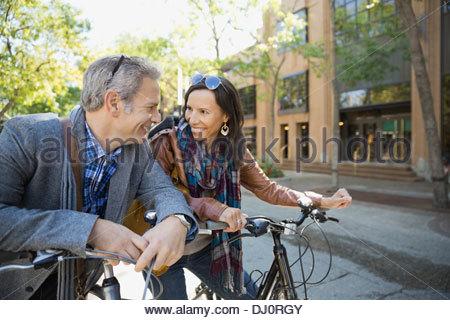 Smiling couple avec des bicyclettes à l'un l'autre Banque D'Images