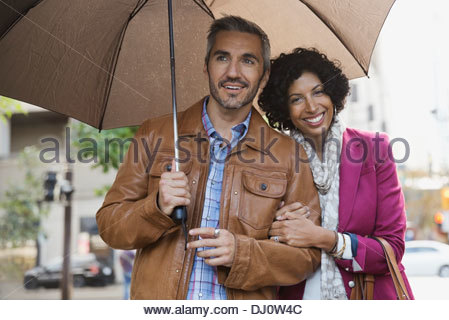 Portrait of couple standing outdoors with umbrella Banque D'Images