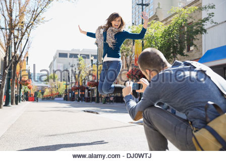 Man photographing woman jumping on city street Banque D'Images