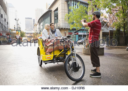 En rickshaw Driver photographing couple Banque D'Images