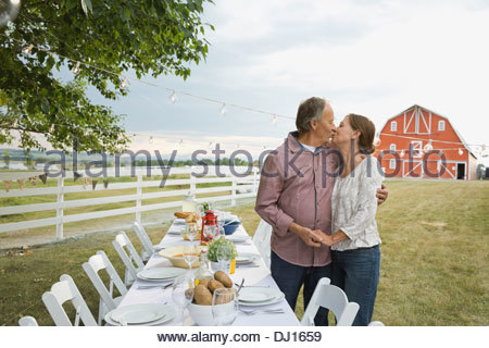 Senior couple kissing by table at home Banque D'Images
