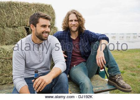 Amis des hommes assis à l'arrière du camion pick-up Banque D'Images