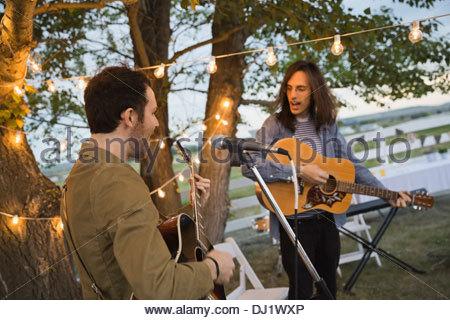 Les hommes de chanter tout en jouant de la guitare au cours de partie en plein air Banque D'Images