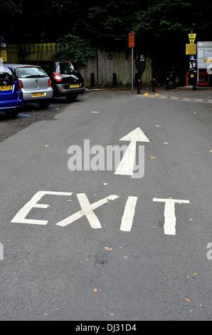 Enseigne de sortie et d'une flèche peinte sur la route du parc automobile Banque D'Images