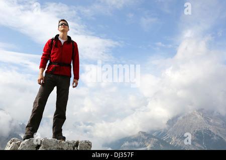 Jeune alpiniste debout sur le sommet d'une montagne et jouissant de la liberté dans les montagnes Banque D'Images