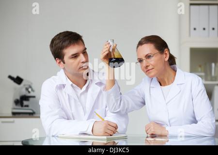 Deux scientifiques à la recherche au flacon en verre avec de l'huile liquide en laboratoire Banque D'Images
