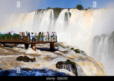 Le Brésil, le Parc National d'Iguaçu: les touristes appréciant les volumes d'eau record de l'Iguassu Falls Banque D'Images