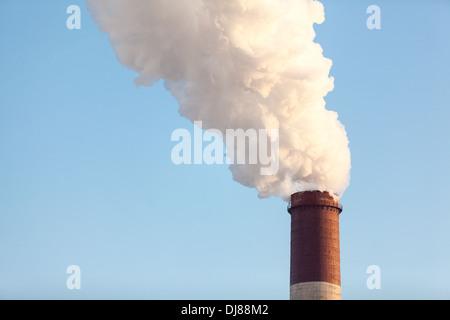 La fumée d'une cheminée sur fond de ciel bleu Banque D'Images
