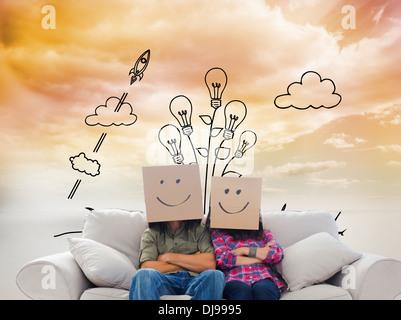 Image composite de silly employés avec bras croisés portant sur leurs têtes des boîtes Banque D'Images