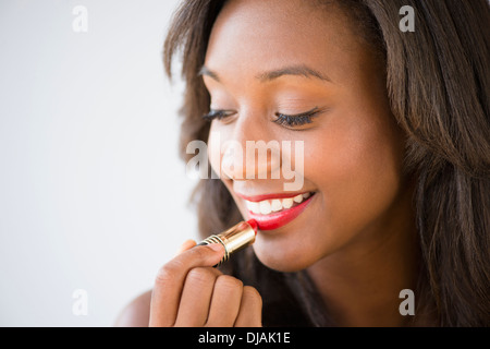 Black woman applying lipstick Banque D'Images