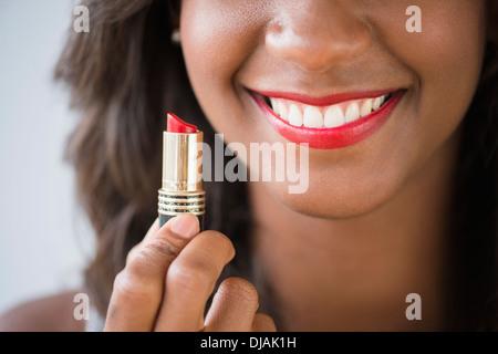 Black woman holding lipstick Banque D'Images
