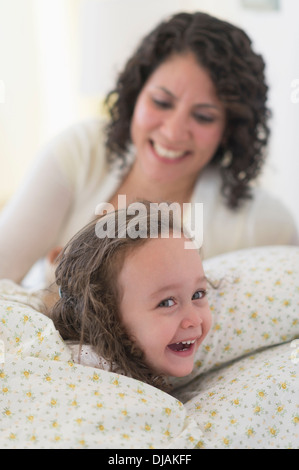 Mixed Race mother putting daughter to bed Banque D'Images