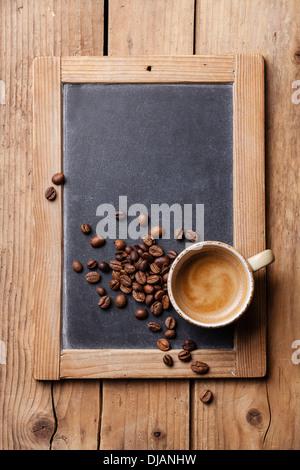 Tasse de café avec café en grains sur tableau noir ardoise vintage Banque D'Images