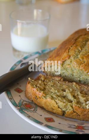 Gros plan d'une miche de pain frais, chaud les courgettes coupées par un couteau et un verre de lait Banque D'Images