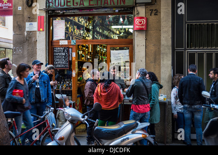 Bodega mécènes sortir dans la rue pour socialiser et de consommer du vin et de la bière, Barcelone, Espagne Banque D'Images