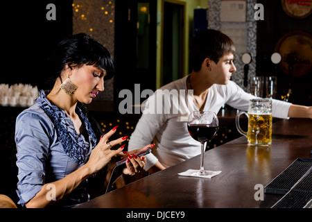 Jeune femme élégante assis au comptoir au bar l'envoi d'un message sms sur son téléphone portable, vue latérale Banque D'Images