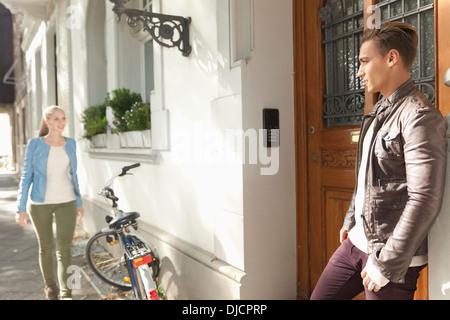 Jeune homme attend sa petite amie en face d'une maison d'habitation Banque D'Images