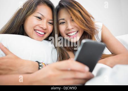 Deux sœurs occasionnels en utilisant un smartphone Banque D'Images
