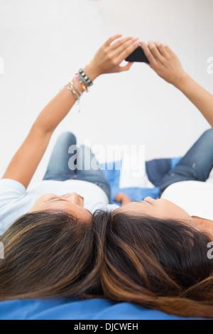 Deux jolies sœurs en utilisant un smartphone Banque D'Images