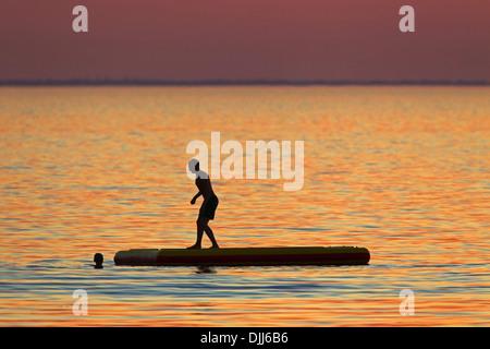 Les nageurs se baigner dans la mer Baltique découpé sur le coucher du soleil, Øresund / Öresund, Suède, Scandinavie Banque D'Images