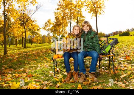 Portrait de deux enfants blonds heureux assis sur le banc du parc en automne Banque D'Images