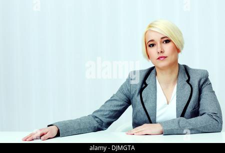 Portrait d'une jeune femme rêveuse assise à la table in office Banque D'Images