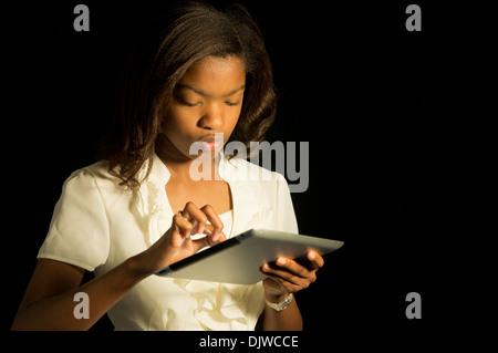 Un African American girl en utilisant sa tablette. Banque D'Images