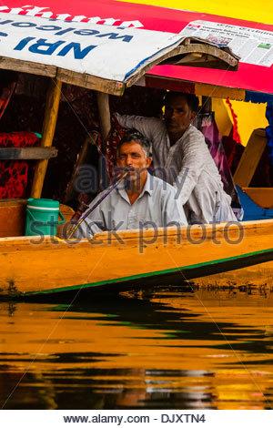 Fumer un narguilé pipe homme à bord d'un bateau (shikara) sur le lac Dal à Srinagar, au Cachemire, l'État de Jammu Banque D'Images