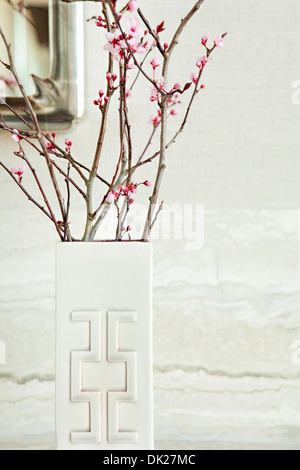 Close up of pink blossoms sur brindilles dans vase blanc moderne Banque D'Images